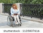 woman on a wheelchair uses a... | Shutterstock . vector #1135837616