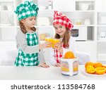 Little chefs making fresh orange juice in the kitchen clinking proudly with the result - stock photo