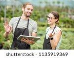 couple of workers in uniform... | Shutterstock . vector #1135919369