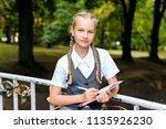 beautiful schoolgirl teenager ... | Shutterstock . vector #1135926230