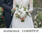 groom in a suit and bride in a... | Shutterstock . vector #1136005919