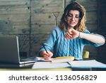 Stock photo caucasian hipster girl checking time on wristwatch feeling unhappy and hurrying up on deadline 1136056829