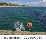 children jumping into the sea... | Shutterstock . vector #1136097350