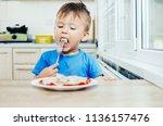 hungry baby eating dumplings in ... | Shutterstock . vector #1136157476