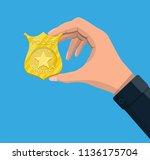 police officer badge in hand.... | Shutterstock .eps vector #1136175704