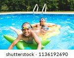 children in outside swimming... | Shutterstock . vector #1136192690
