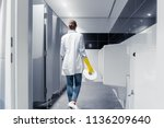 janitor woman changing paper in ... | Shutterstock . vector #1136209640