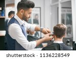 barber doing new haircut for... | Shutterstock . vector #1136228549