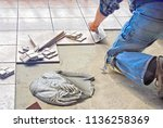 man using trowel to lay floor... | Shutterstock . vector #1136258369
