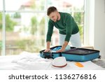 young man packing suitcase for... | Shutterstock . vector #1136276816