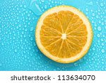 slice of lime with drop on blue