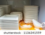 white plates on a shelf in a... | Shutterstock . vector #1136341559