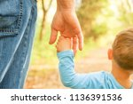 the parent holding the child's... | Shutterstock . vector #1136391536