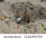 children dig a hole in the sand ... | Shutterstock . vector #1136395733