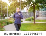 young fitness woman jogging in... | Shutterstock . vector #1136446949