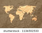 yellow world map on brown... | Shutterstock . vector #1136502533