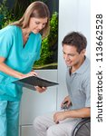 Female dentist taking an appointment of male patient on clipboard at clinic - stock photo