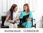 Female dentist showing something to young patient on clipboard in clinic - stock photo