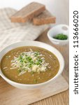 A bowl a lentil soup with cheese and green onions - stock photo