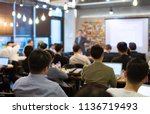 Small photo of Audience Listens to Lecturer at a Conference Meeting Seminar Training. Group of People Hear Presenter Give Speech . Corporate Manager Speaker Gives Business Technology and Economic Forecast.