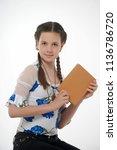 young pretty schoolgirl sitting ... | Shutterstock . vector #1136786720