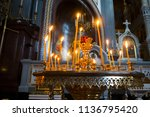 many burning wax candles in the ... | Shutterstock . vector #1136795420
