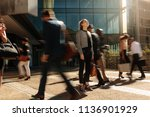 woman standing amidst a busy... | Shutterstock . vector #1136901929