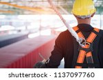 Construction worker wearing safety harness and safety line working at high place - stock photo
