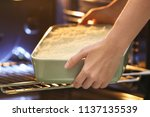 woman putting baking dish with... | Shutterstock . vector #1137135539