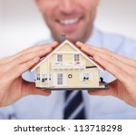 Portrait Of A Cheerful Architect Holding A House Model - stock photo