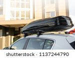 Stock photo large black box trunk on the roof of a white car travel and accessories for transportation 1137244790