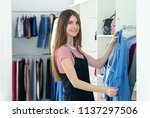 young woman chooses new clothes ...   Shutterstock . vector #1137297506