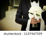 bridegroom holding flower... | Shutterstock . vector #1137467339