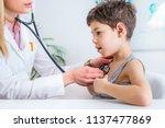 pediatrician examining boy with ... | Shutterstock . vector #1137477869