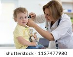 doctor examines kid's ear with... | Shutterstock . vector #1137477980