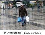 an elderly man walks as he... | Shutterstock . vector #1137824333