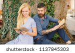 Small photo of Date and love concept. Couple in love sits outdoor with old books, nature background, defocused. Girl with happy face and bearded man reading poems. Romantic couple holds old books with poems.
