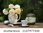 Stock photo gorgeous bouquet of fresh roses in old antique faience ceramic porcelain pitcher floral pattern 1137977330