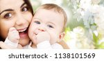 Stock photo family and motherhood concept happy smiling young mother with little baby over cherry blossom 1138101569