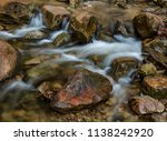 A reddish colored rock has water flowing around it in Parfrey