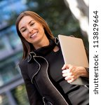 Business woman carrying a laptop out in the city - stock photo