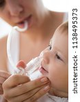 mother cleaning babies nose.... | Shutterstock . vector #1138495373