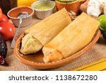 Typical Mexican food dishes with sauces on colorful table. Red and green mole tamales