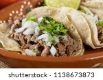 Typical Mexican food dishes with sauces on colorful table. Roast beef tacos