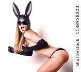 Small photo of beautiful woman in black panties, satin gloves and a plastic rabbit mask stands sideways stands in the fighting stance opening her mouth in amazement simulates running on the spot
