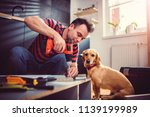 man with small yellow dog... | Shutterstock . vector #1139199989