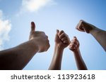 Small photo of All thumbs up on cloudy sky in the background