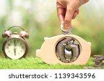 woman hand putting a coins...   Shutterstock . vector #1139343596