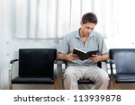 Young man reading book in doctor's waiting room - stock photo