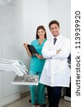 Portrait of young male dentist and assistant standing in dental clinic - stock photo